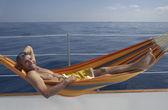 Man laying in hammock on boat — Stock Photo