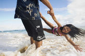 Pacific Islander father and daughter playing at beach — Stock Photo