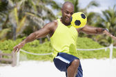 African American man bouncing soccer ball on knee — Stock Photo