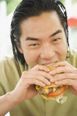 Asian man eating hamburger — Stock Photo