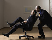 African American businessman pushing coworker in chair — Stock Photo
