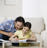 Asian father helping daughter with homework — Stock Photo