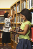 African American girl reading library book — Stock Photo