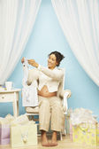 Pregnant Mixed Race woman opening gifts — Stock Photo
