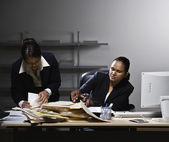 Multi-ethnic businesswomen looking through paperwork — Stock Photo