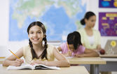 Hispanic girl writing in classroom — Stock Photo