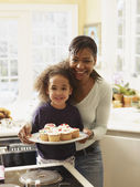 African mother and daughter with tray of cupcakes — Stock Photo