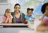 Mixed Race female teacher and students behind desk — Stock Photo