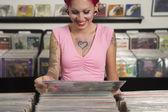 Tattooed Hispanic woman looking at record albums — Stock Photo