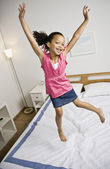 Mixed Race girl jumping on bed — Stock Photo