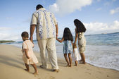 Pacific Islander family walking on beach — Stock Photo