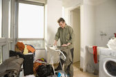 Man ironing clothing in laundry room — Stock Photo