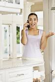 Hispanic woman talking on telephone — Stock Photo