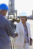 African American businesswoman and construction worker shaking hands — Stock Photo