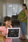 Hispanic girl holding mother's ultrasound — Stock Photo