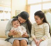 Hispanic grandmother and grandchildren on sofa — Stock Photo