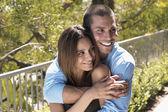 Multi-ethnic couple hugging outdoors — Stock Photo