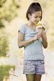 Hispanic girl smelling cut flowers — Stock Photo
