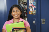Hispanic teenaged girl in front of school locker — Stock Photo