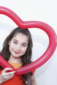 Hispanic girl holding heart-shaped balloon — Stock Photo