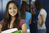 Asian teenaged girl in front of school lockers — Stock Photo