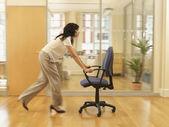 Hispanic businesswoman pushing office chair — Stock Photo