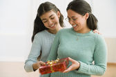 Hispanic mother and daughter exchanging gift — Stock Photo