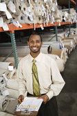 African American sales representative in carpet warehouse — Stock Photo