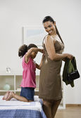 Mixed Race girl zipping mother's dress — Stock Photo