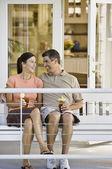 Multi-ethnic couple sitting on porch swing — Stock Photo