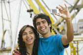 Multi-ethnic teenaged couple taking own photograph — Stock Photo