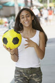 Mixed Race teenaged girl holding soccer ball — Stock Photo