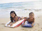 Pacific Islander siblings laying on boogie boards — Stock Photo