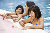 Hispanic teenaged girls painting fingernails in swimming pool — Stock Photo