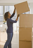 African woman stacking moving boxes — Stock Photo