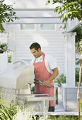 Hispanic man next to barbecue — Stock Photo