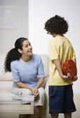Hispanic boy surprising mother with gift — Stock Photo