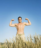 Pacific Islander man flexing in field — Stock Photo