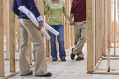 Asian couple and architect in new construction — Stock Photo