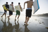 Multi-ethnic men running with surfboards — Stock Photo