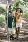 Mixed Race siblings holding walking sticks — Stock Photo