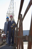 Multi-ethnic male construction workers in front of crane — Stock Photo