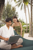 Asian couple looking at laptop — Stock Photo