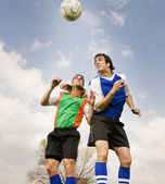 Multi-ethnic male soccer players jumping for ball — Foto de Stock