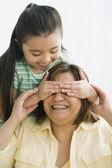 Hispanic girl covering mother's eyes — Foto de Stock