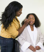 African woman having makeup applied — Stock Photo