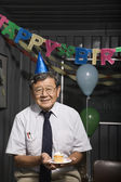 Senior Asian businessman holding birthday cupcake — Stock Photo