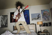 Boy playing guitar and jumping on bed — Stock Photo