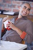 African American man eating take out food — Stock Photo