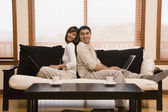 Hispanic couple sitting back to back on sofa — Stock Photo